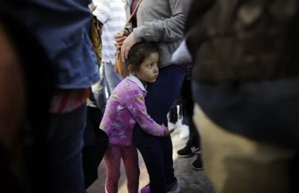 6月13日,在美墨边境墨西哥一侧的蒂华纳,一名小女孩抱着母亲。为了能够进入美国,她们已在这里滞留一周。新华社/美联