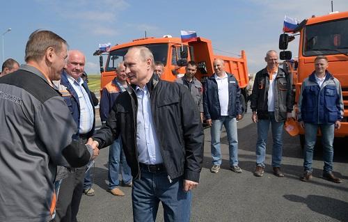 普京15日在大桥开通仪式前与工人握手(路透社)