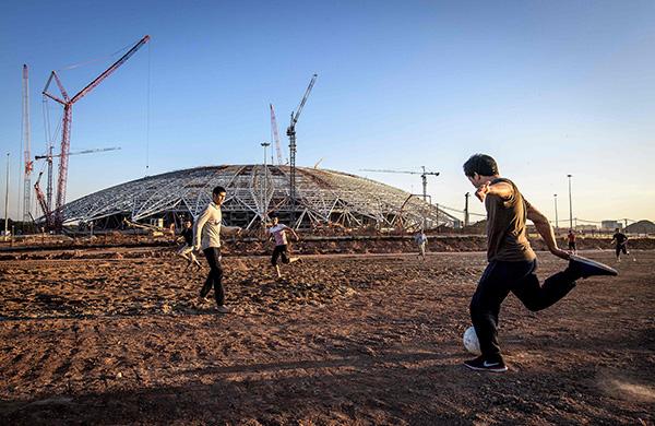 孩子们在未建成的球场工地外踢球。