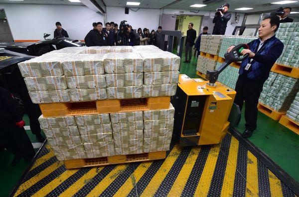 韩国企划财政部2015年3月26日晚宣布,韩国决定申请加入亚洲基础设施投资银行(亚投行)。这张资料照片显示,在位于韩国首尔的韩国中央银行,一名银行的工作人员转运成捆的韩元纸钞。新华社/法新