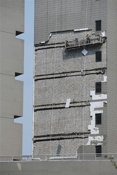 7月6日15时左右,顺义区悦君家园8号楼,工人在清理事发外墙上的保温层。新京报记者 朱骏 摄