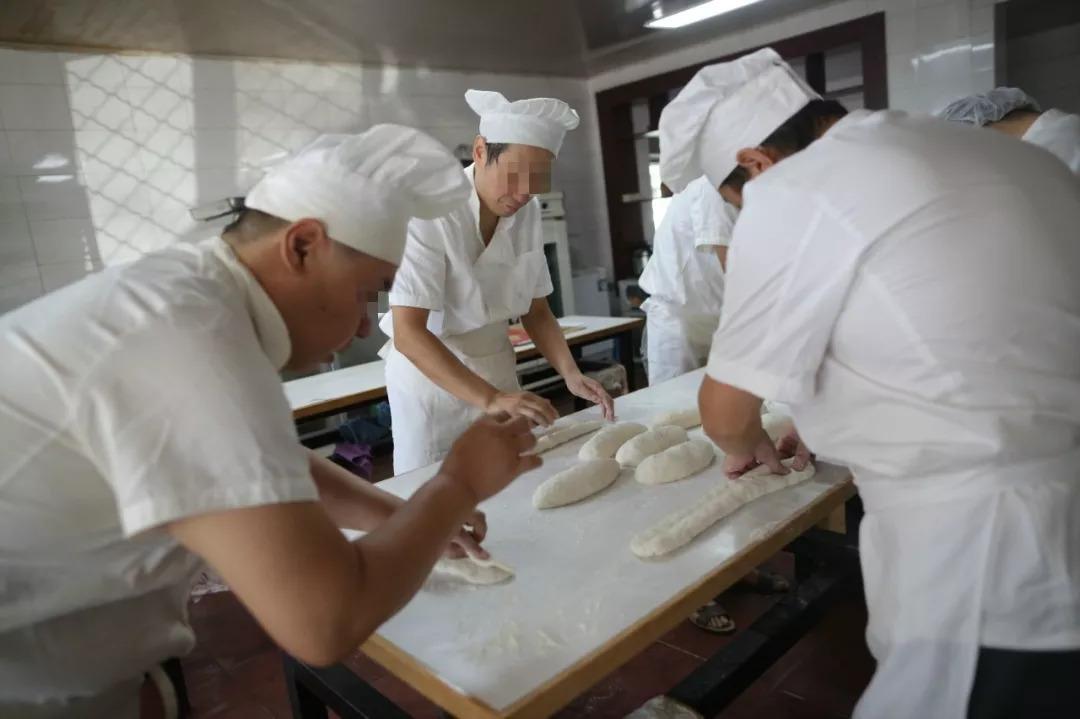 """2018年9月4日,朝阳区精神病托管服务中心,参与""""疯狂面包房""""治疗项目的托管人在老师的带领下制作面包。新京报记者 侯少卿 摄"""