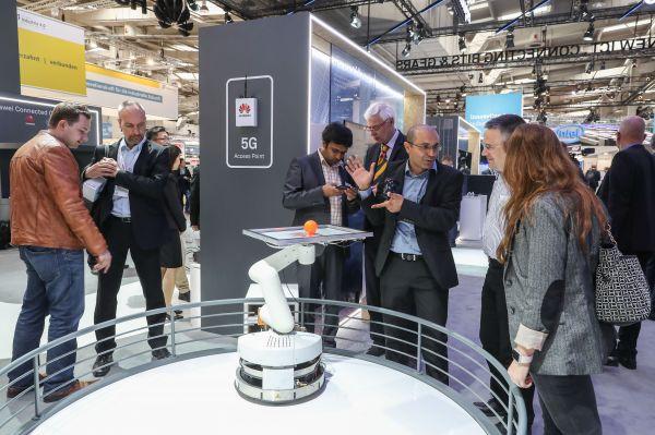 4月24日,在德国汉诺威,参观者们观看华为公司展区展出的运用5G技术操控的机器人。(新华社)