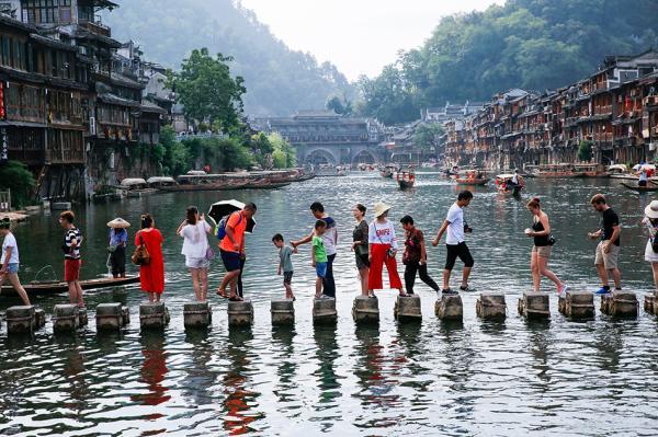 2017年8月5日,游客在湖南凤凰古城沱江上参观游览。视觉中国 资料图