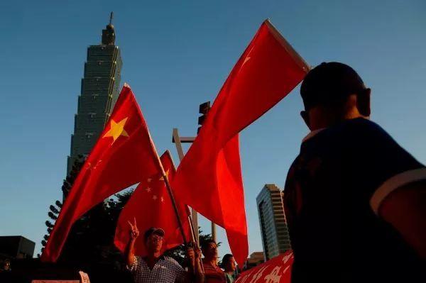 ▲台北街头,台湾民众手持五星红旗。(图片来源:台媒)