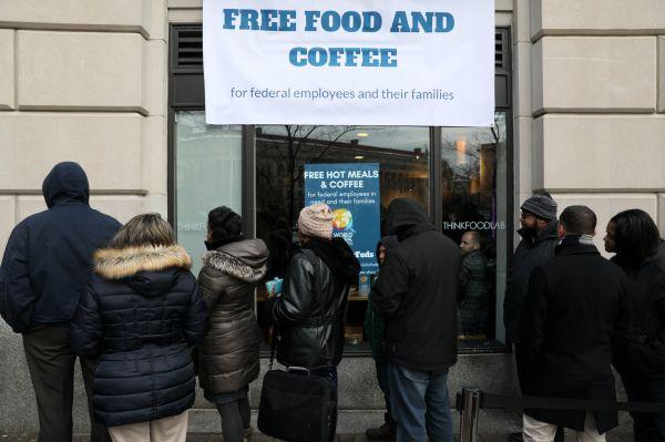 受美国政府关门影响的联邦雇员16日在华盛顿排队领取由非营利组织提供的免费食物和咖啡。(路透社)