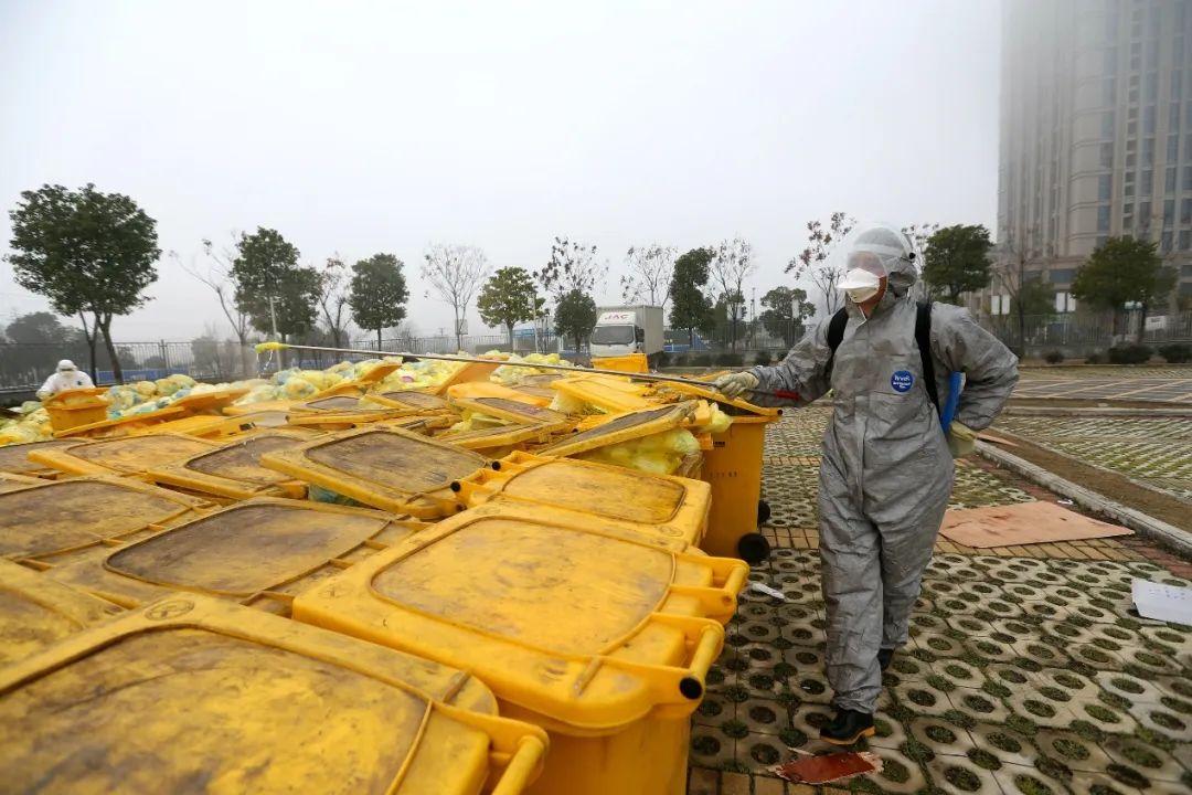 一名医院临时转岗的绿化工人正在对临时露天存放的医疗废物进行消毒,这样的工作全天进行。由于人手不足,一些原本在医院后勤工作的员工主动要求转岗,在一线处置医疗废物。(摄影:崔萌)
