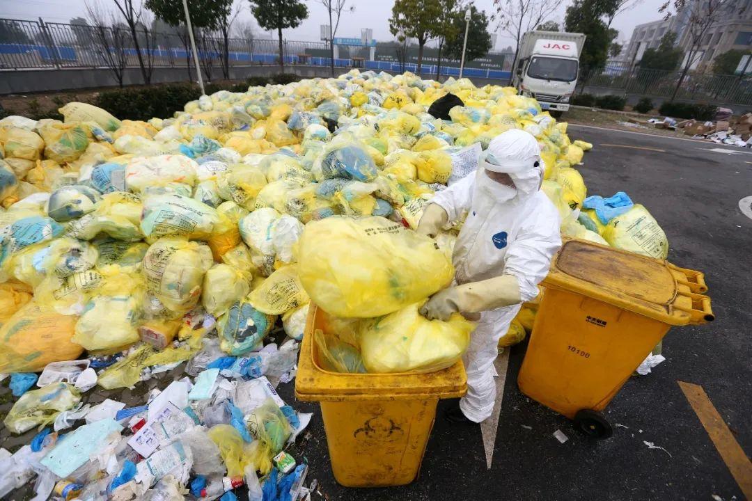 一名后勤人员正在将临时露天存放的医疗废物装桶,等待转运车辆的到来。(摄影:崔萌)