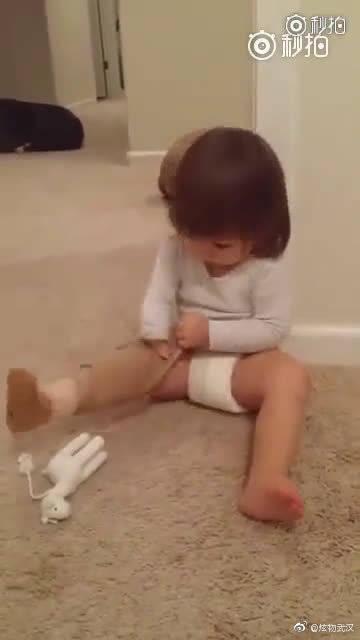 一个小女孩在妈妈的鼓励下,乖乖把义肢戴上,