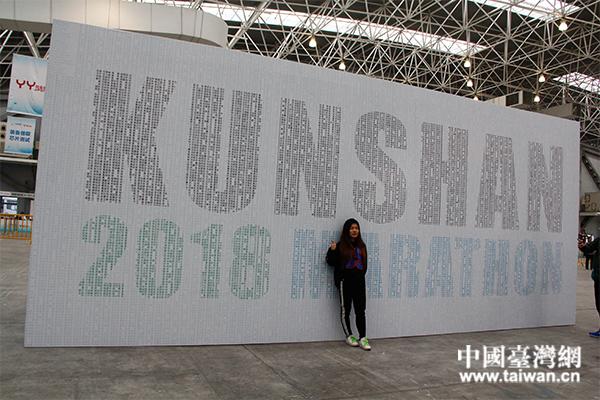 一名观众在昆山马拉松姓名墙前合影留念.(中国台湾网 汪明珠 摄)图片