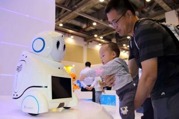 ▲5月10日,2018全球人工智能产品应用博览会在江苏省苏州市开幕,1000多种人工智能新产品集中亮相。图为博览会上一名小朋友被一款儿童陪伴机器人所吸引。(王建康 摄)