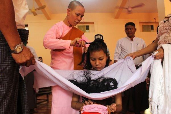 图为在泼水节期间,一名年轻女子剪掉头发。