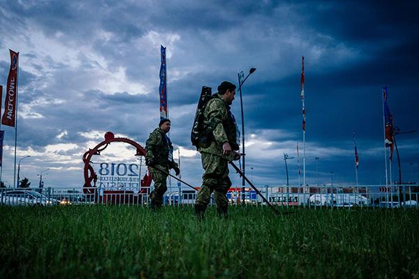 陆军工兵在比赛场馆的草坪里扫雷。