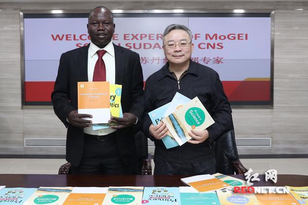南苏丹教育部次长迈克尔·隆格里奥和中南出版传媒集团董事、总经理丁双平展示双方合作开发的教材。图自红网