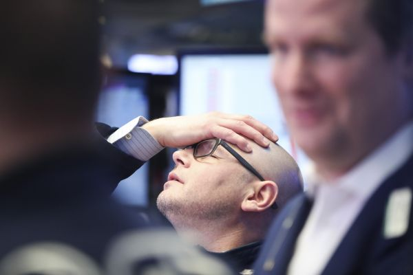 资料图:纽约证券交易所的一名交易员在股市收盘后小憩。