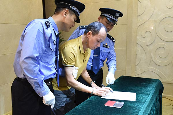 """""""红通人员""""梁泽宁在逮捕证上签字(深圳市纪委监委 倪勋 摄)"""