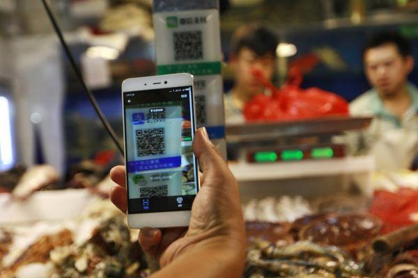 在北京一家超市,顾客用智能手机扫描二维码支付。(香港《南华早报》网站)