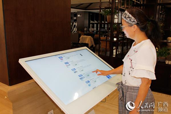 南宁市民张女士使用电子触摸屏查阅资料
