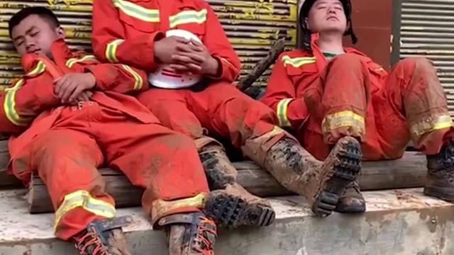 救援现场下起了大雨。救援人员进行短暂休息,他们全身湿透,衣服