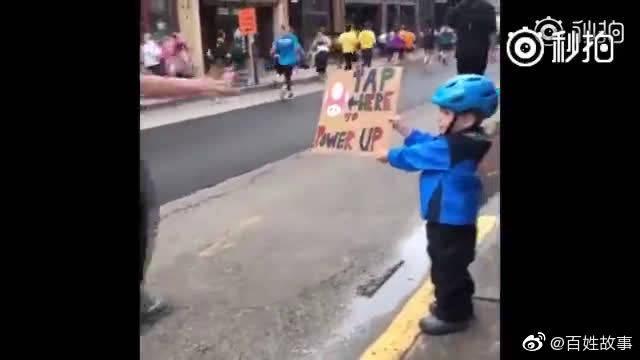 马拉松比赛中,一个小男孩举着牌子为选手们加油,牌子上画着马里奥