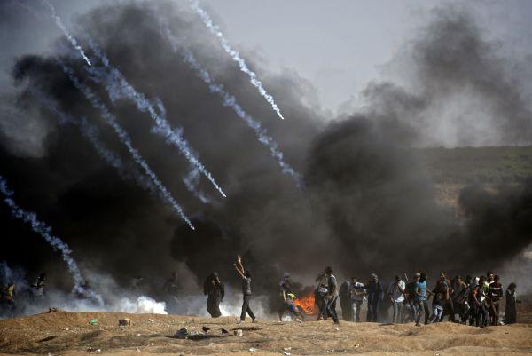 5月14日,在加沙地带与以色列接壤的边境地区,巴勒斯坦抗议者在示威活动中躲避以军的催泪弹。(新华)