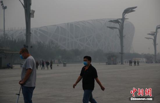 资料图:游客戴口罩在北京奥林匹克公园游玩。中新社发 刘关关 摄
