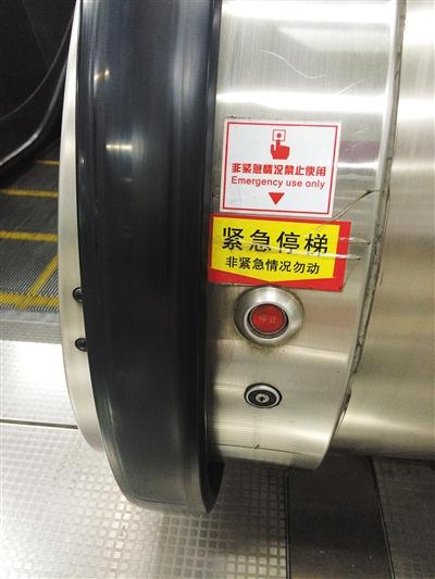 """在扶梯扶手带入口处,一般会有一个""""紧急停梯""""按钮,遇意外情况可紧急停住电梯。新京报记者 彭子洋 摄"""