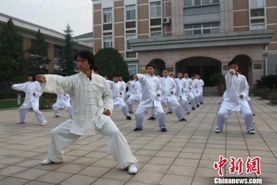 为,武汉外国语学校美加分校学生在学校课堂学习武当武术.   摄 -