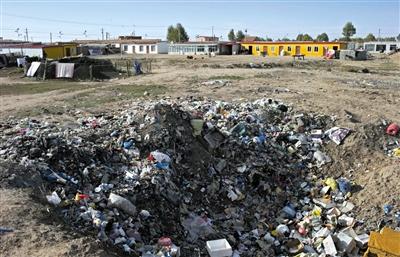 共和县倒淌河镇种羊场所在的村中一处垃圾坑里堆着垃圾。最近的牧民家离这里约二十米。