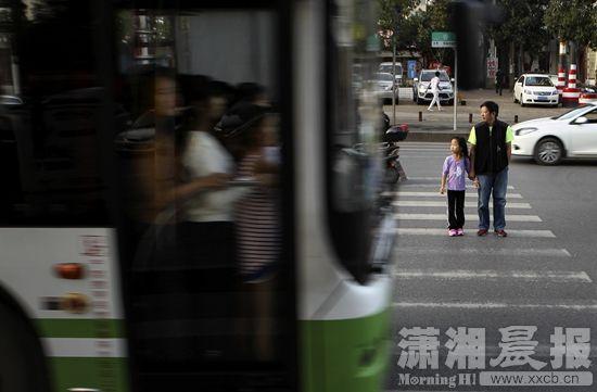 10月11日,长沙香樟路,市民小心行走在斑马线上,公交车正常行驶通过。图/潇湘晨报记者陈正