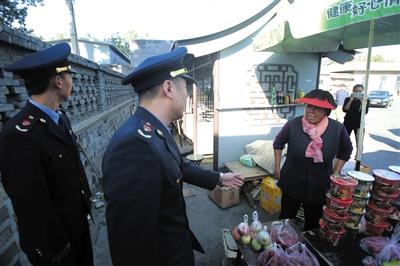 昨日,明十三陵景区,执法人员让摊贩出示营业执照。