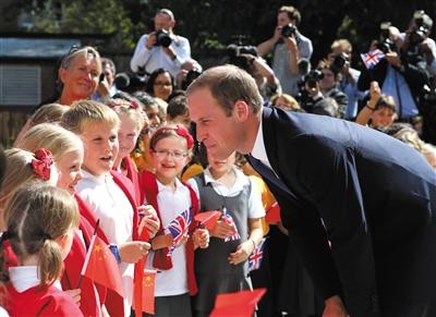 2014年9月8日,在英国潘迪生牛津大学中国中心揭幕仪式前,小学生挥舞中英两国国旗欢迎威廉王子(右)。