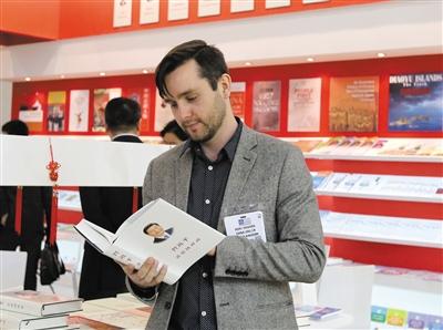 2015年4月14日,在英国伦敦书展,一名英国读者翻阅《习近平谈治国理政》(繁体中文版)一书。