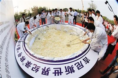 """22日,一些学生正在扬州市宋夹城同时挥勺翻锅炒制""""最大份炒饭""""。 图/CFP"""
