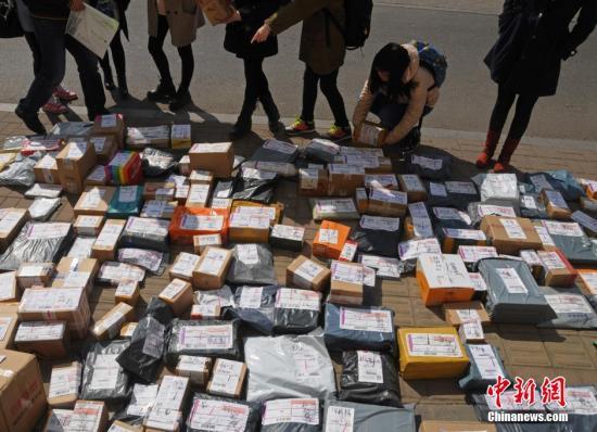 3月10日,山西太原一高校外,学生们在地摊上找寻各自的快递。武俊杰