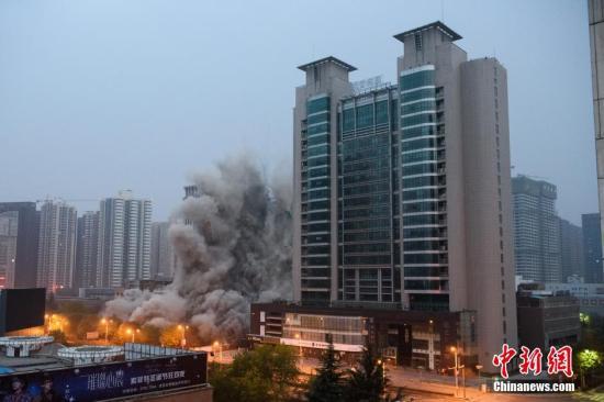 11月15日上午7时,西安市高新区高新二路一座高118米的高楼成功实施了爆破拆除,约10秒之后大楼顺利坍塌。图片来源:视觉中国