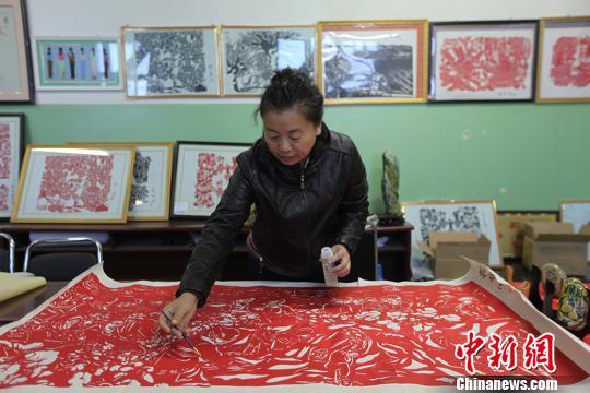 """图为巨幅剪纸""""复兴之梦""""作者康艳在对剪纸作品进行维护. 李江帆"""