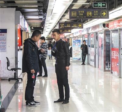 """11月17日,中关村科贸大厦地下一层,一位""""导购""""正在拉客。新京报记者 彭子洋 摄"""