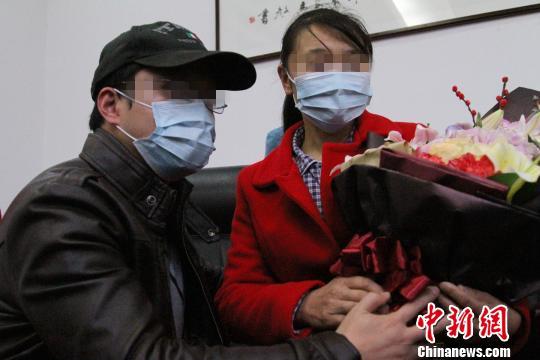 患者丈夫向患者母亲献花表示感谢。 记者 张远 摄
