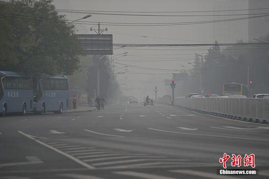 材料图:2015年11月14日,北京市延续遭逢中度至重度雾霾净化,郊区能见度低。图为北京东部城区陌头能见度缺乏百米。 中新网记者 金硕 摄
