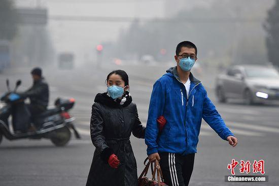 资料图:北京街头,行人佩戴防护出行。中新网记者 金硕 摄