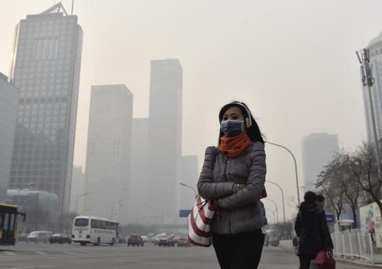 ■一名戴口罩的行人在雾霾下的北京街头行走。新华社发