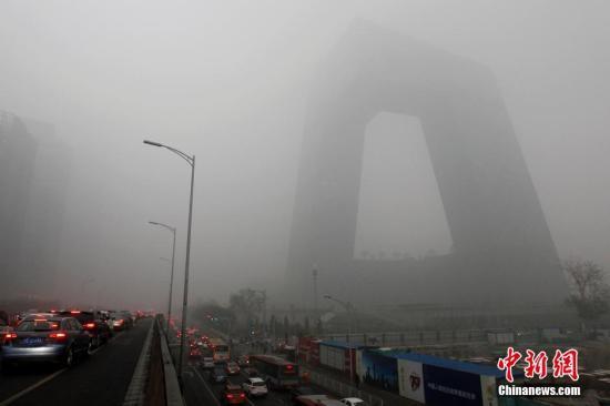 """12月1日,北京市区陷入重度雾霾,白昼如夜,能见度极差。从11月27日开始,发生在华北地区的这轮大范围严重污染过程,已持续4天,为今年以来最严重的污染过程。盘踞多天的重霾,丝毫没有散场的趋势。图为东三环国贸附近建筑""""隐身""""。 中新社记者 富田 摄"""