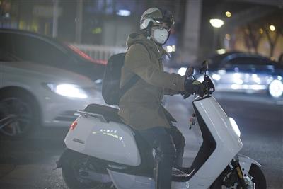 昨夜,蒲黄榆,一位路人戴口罩骑行。新京报记者 王嘉宁 摄