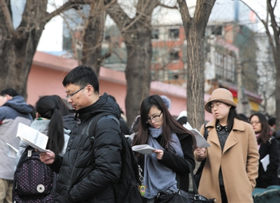 昨日,2016年北京公务员考试呼家楼中学考点。开考前,考生在考场外阅读材料。新京报记者 卢淑婵 摄