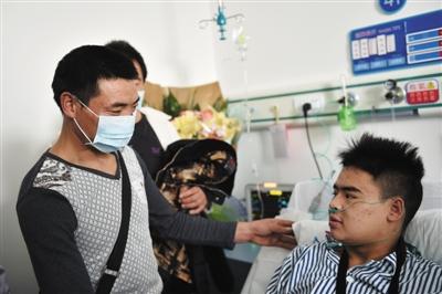 12月24日,在深圳市光明新区中心医院,田祖龙(左)见到病床上的儿子田泽明。新华社记者 毛思倩 摄