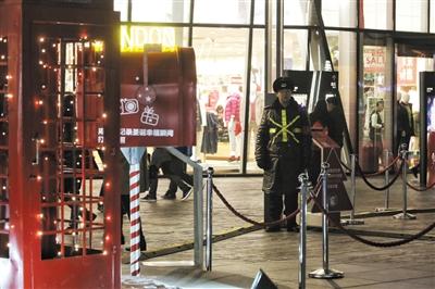 昨晚8时,在三里屯的一家商铺前,一名保安站在圣诞节装饰前站岗。