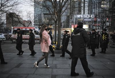 昨日下午,一名女子从正在巡逻的民警和保安身旁走过。