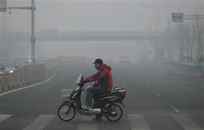 12月25日,菜市口大街,一位市民戴着口罩过马路。当天京津冀多地空气重污染。昨日发布的《京津冀协同发展生态环境保护规划》明确,到2020年,京津冀地区PM2.5年均浓度要比2013年下降40%左右。新京报记者 薛珺 摄