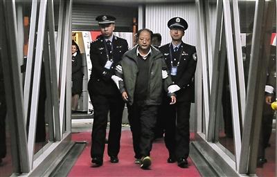 """昨日,外逃6年的""""百名红通""""10号嫌犯裴健强被抓获归案。图为裴健强(中)被执法人员带离北京首都国际机场。新华社发"""